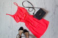 Red sundress, black handbag and shoes on a wooden background. Fashionable concept Royalty Free Stock Photo