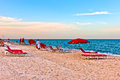 Red sunloungers and parasols at the beach in sunset light Royalty Free Stock Images