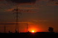 Red sunset over power poles and a tree view of Stock Image