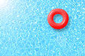 Red swimming pool ring float in blue water and sun bright. Royalty Free Stock Photo