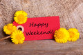 Red tag with happy weekend a the words on it and yellow flowers on wood Stock Images