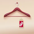 Red tag with sale sign hanging on wooden hanger Stock Photo