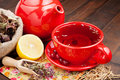 Red tea cup and teapot, healing herbs and lemon Royalty Free Stock Image