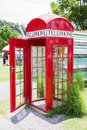 Red telephone booth in the garden Stock Photo