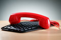 Red telephone receiver on keyboard Royalty Free Stock Photo