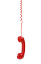 Red telephone receiver old fashioned hanging on cable isolated on a white Royalty Free Stock Photo
