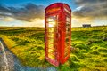 Red telephone urban box in the middle of a green countryside concept for synergy between modern city and rural area the technology Stock Image