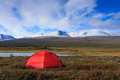 Red tent camping with a in arctic wilderness with snow capped mountains Stock Photo