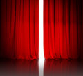 Red theater or cinema curtain slightly open and white light behind it Royalty Free Stock Photography