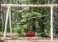 Red tire swing single hanging from a log frame surrounded by green trees in the summer Stock Photos
