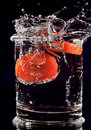Red tomato falling down in water glass Royalty Free Stock Photo
