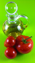Red tomato and olive oil on green background Stock Photos