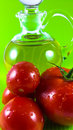 Red tomato and olive oil on green background Royalty Free Stock Photo