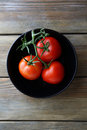 Red tomatoes in black bowl top view Stock Photos