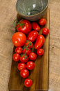 Red tomatoes and a green bowl on wood and canvas Royalty Free Stock Images