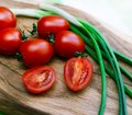 Red tomatoes and green onions on the cutting board close up Royalty Free Stock Photography