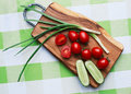 Red tomatoes and green onions on cutting board closeup close up Stock Image