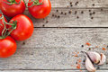 Red tomatoes with pepper and garlic on old wood Royalty Free Stock Photo