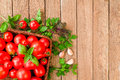 Red tomatoes in a wicker basket on a wooden table Royalty Free Stock Photo