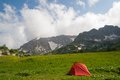 Red tourist tent is against mountains at morning time Stock Images