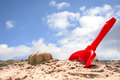 Red toy shovel and molded sand on the beach against the blue sky Royalty Free Stock Photo