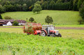 Red tractor in the field near house