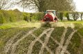 Red tractor spreading spreading slurry on fields Royalty Free Stock Photo