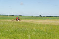 Red tractor ted hay dry grass in agriculture field Royalty Free Stock Photo