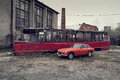 Red tram and classic british mg old mgb gt against old factory Royalty Free Stock Image