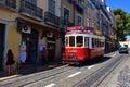 Red tram on a narrow street in Lisbon, Portugal