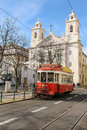 Red tram and st paul church lisbon portugal a passing by sao paulo portugalrn Royalty Free Stock Photography