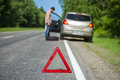 Red triangle sign and driver with spare wheel broken car male focus on warning Stock Images