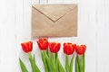 Red tulips and a card in an envelope Royalty Free Stock Photo