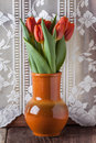 Red tulips in ceramic jar Stock Images