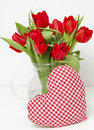 Red tulips and heart-shaped pillow Royalty Free Stock Photos
