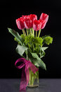 Red tulips in vase a beautiful bunch of a with a bow Royalty Free Stock Photos