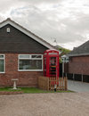 Red uk telephone box outside of house