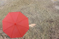 Red umbrella and a hand of man standing on soil dry pond and han Royalty Free Stock Photo