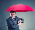 Red umbrella office worker hiding under an and waiting for the rain Royalty Free Stock Photography