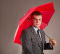 Red umbrella office worker hiding under an and waiting for the rain Royalty Free Stock Image