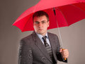 Red umbrella office worker hiding under an and waiting for the rain Stock Photography