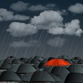 Red umbrella over many dark ones standing out from the crowd high angle view of vector illustration Stock Photos