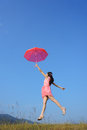Red umbrella woman jump to sky Stock Photos