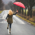 Red umbrella woman walking under the rain with Royalty Free Stock Photography