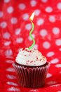 Red velvet cupcake with green candle Royalty Free Stock Images