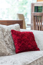 Red velvet pillow a closeup of an ecru sofa with a Royalty Free Stock Image