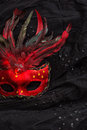 Red venetian carnival mask with feather over black Royalty Free Stock Photo