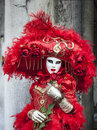 Red venetian disguise venice italy february th beautiful posing with a rose in san marco square during the venice carnival days Royalty Free Stock Photos