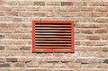 Red ventilation grill on a wall made of bricks Stock Photo