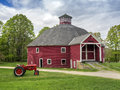 Red vermont octagonal barn new england with vintage tractor in foreground Royalty Free Stock Images